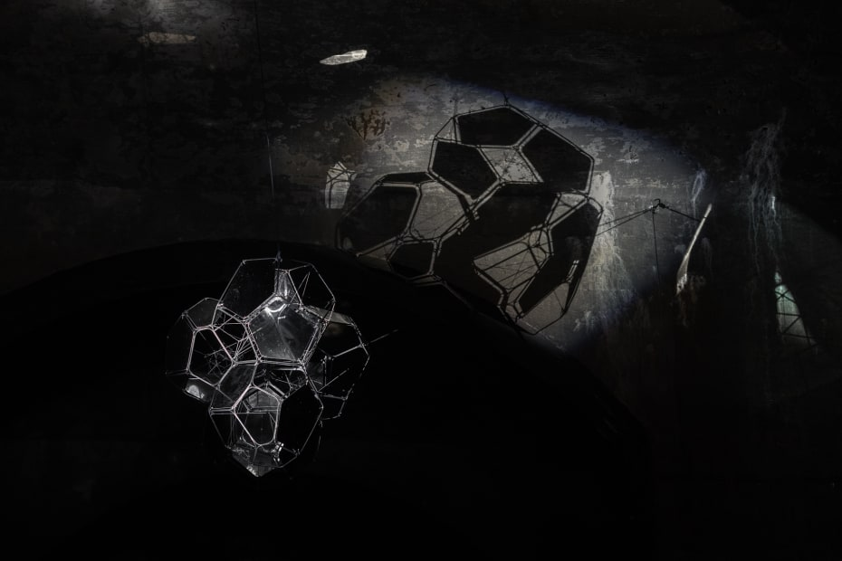 image of Saraceno sculptures hanging in dark room over water