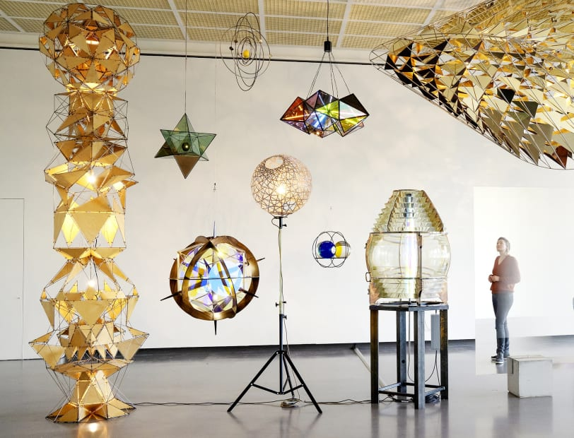 installation of multiple geometric sculptures hanging together