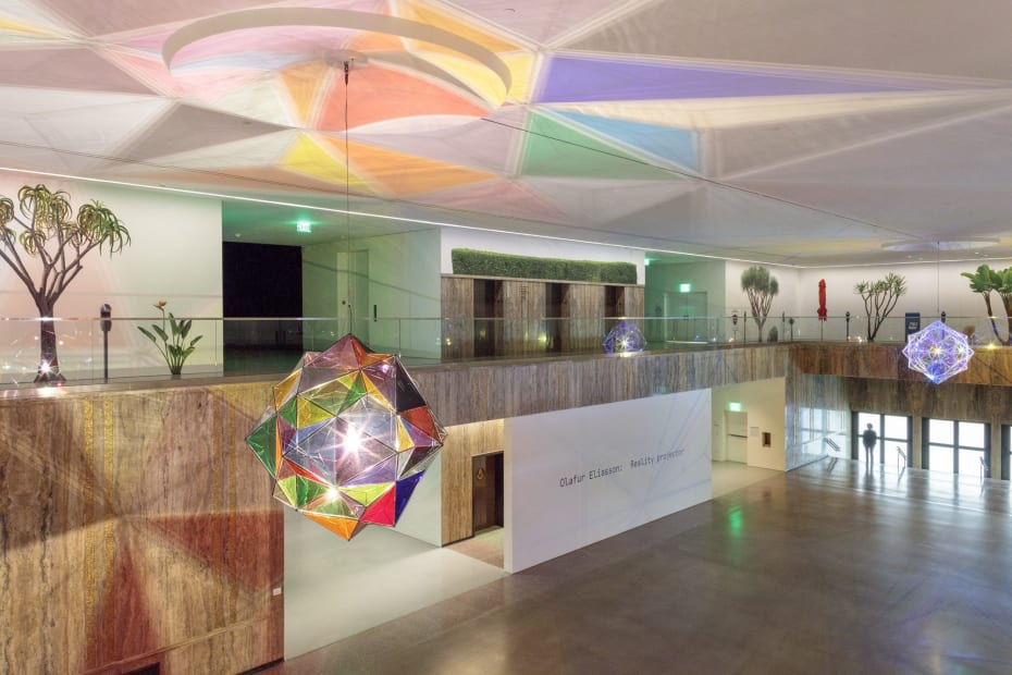 image of installation view, with two large geometric lamps