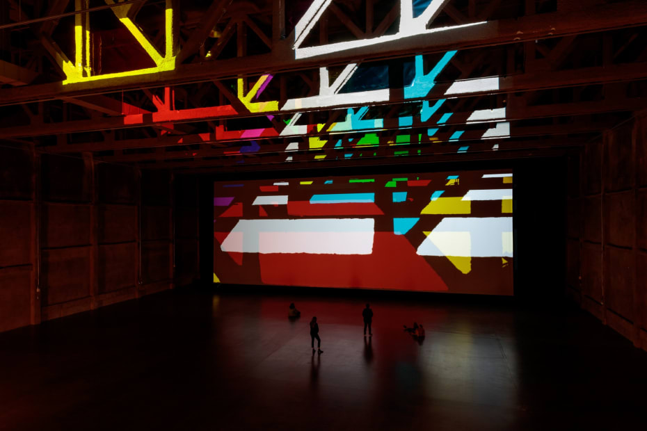 image of installation view large space with color filters and lights projecting onto the wall