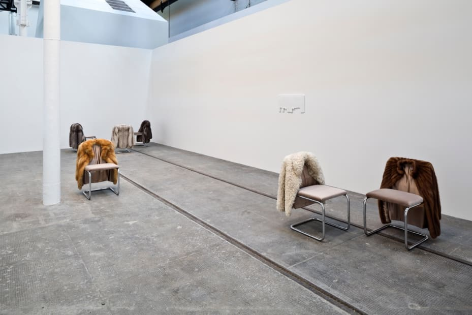 image of chairs with fur coats hanging off of them
