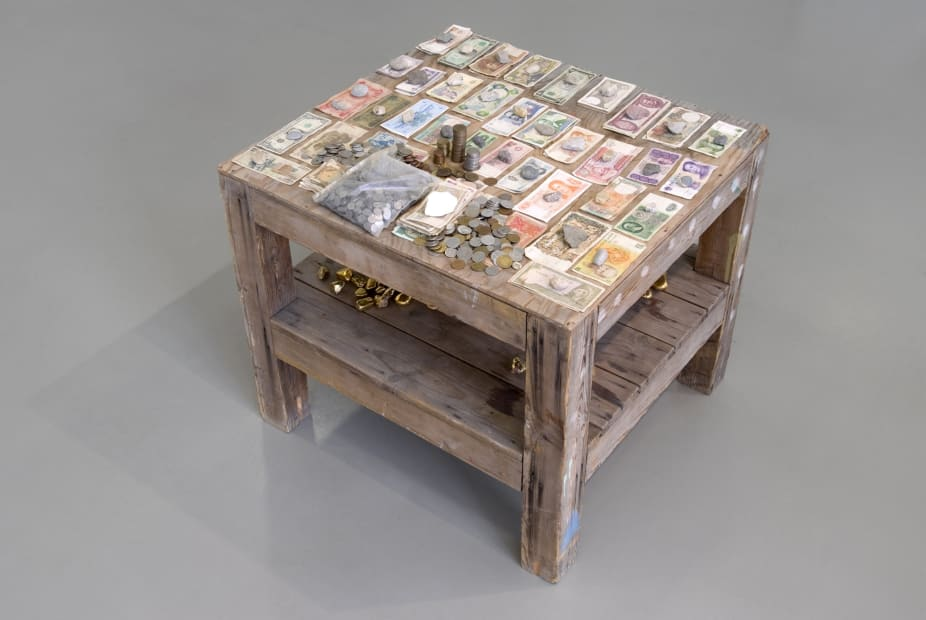 installation view of sculptures, currency on the table