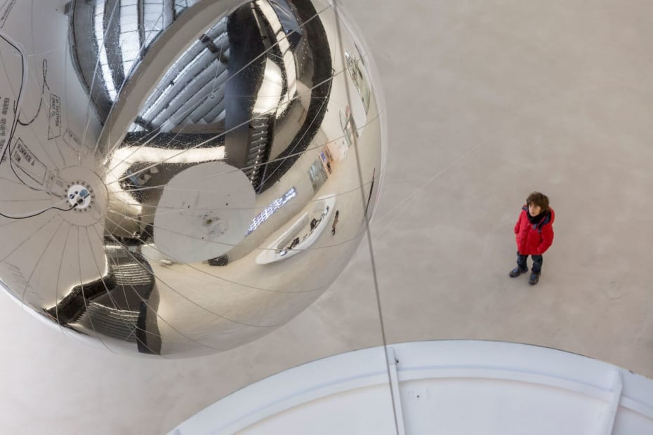 Person in a red coat looking up at the giant silver sphere