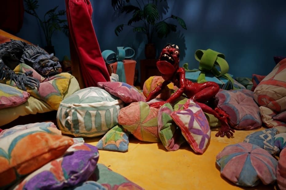 Djurberg and Berg colorful soft puppet sculptures installed in a whimsical corner of the museum gallery full of pillows and cushions