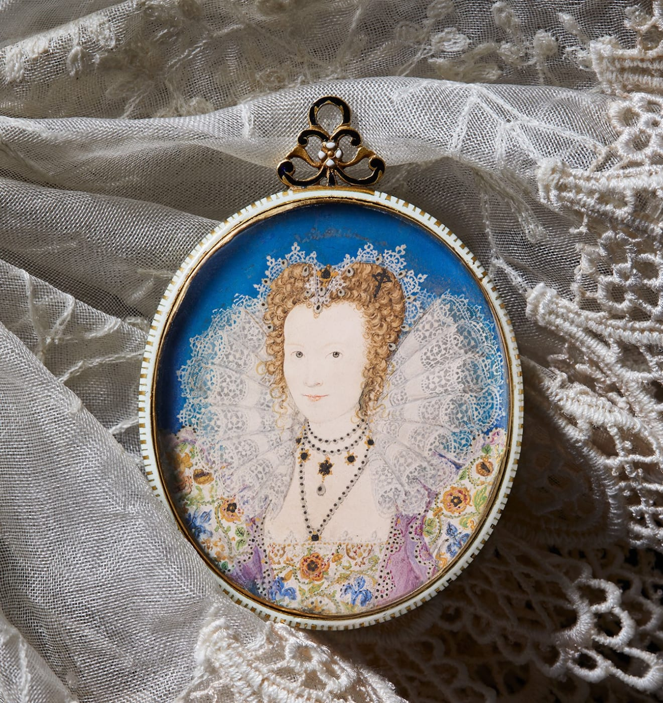 A portrait miniature of a Tudor Lady in Court. She wears a large lace ruff, with a floral dress against a bright blue backgound This artwork by Nicholas Hilliard has sold.