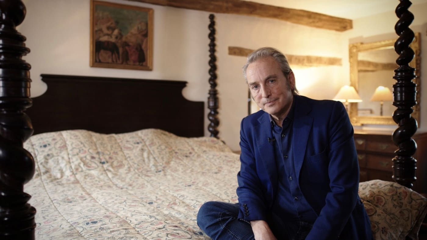 Philip Mould sitting on four poster bed in front of Roger Fry Bloomsbury painting