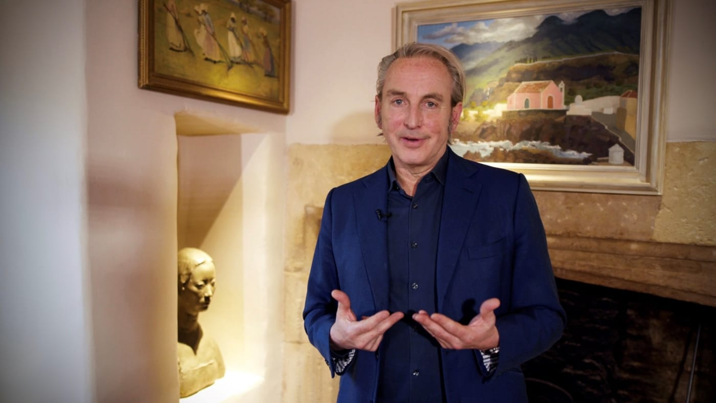Philip Mould in front of two paintings by Cedric Morris and Dora Noyes in his home