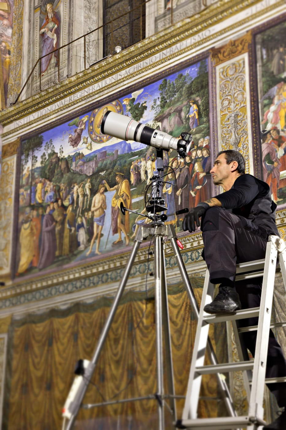 Photographer sitting on a ladder taking photographs of the Sistine Chapel for the new publication