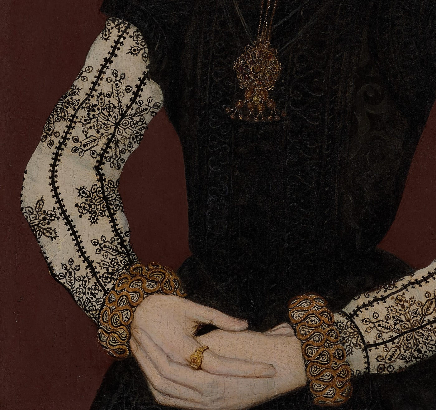 clasped hands of young woman dressed in embroidered dress painted by a tudor artist