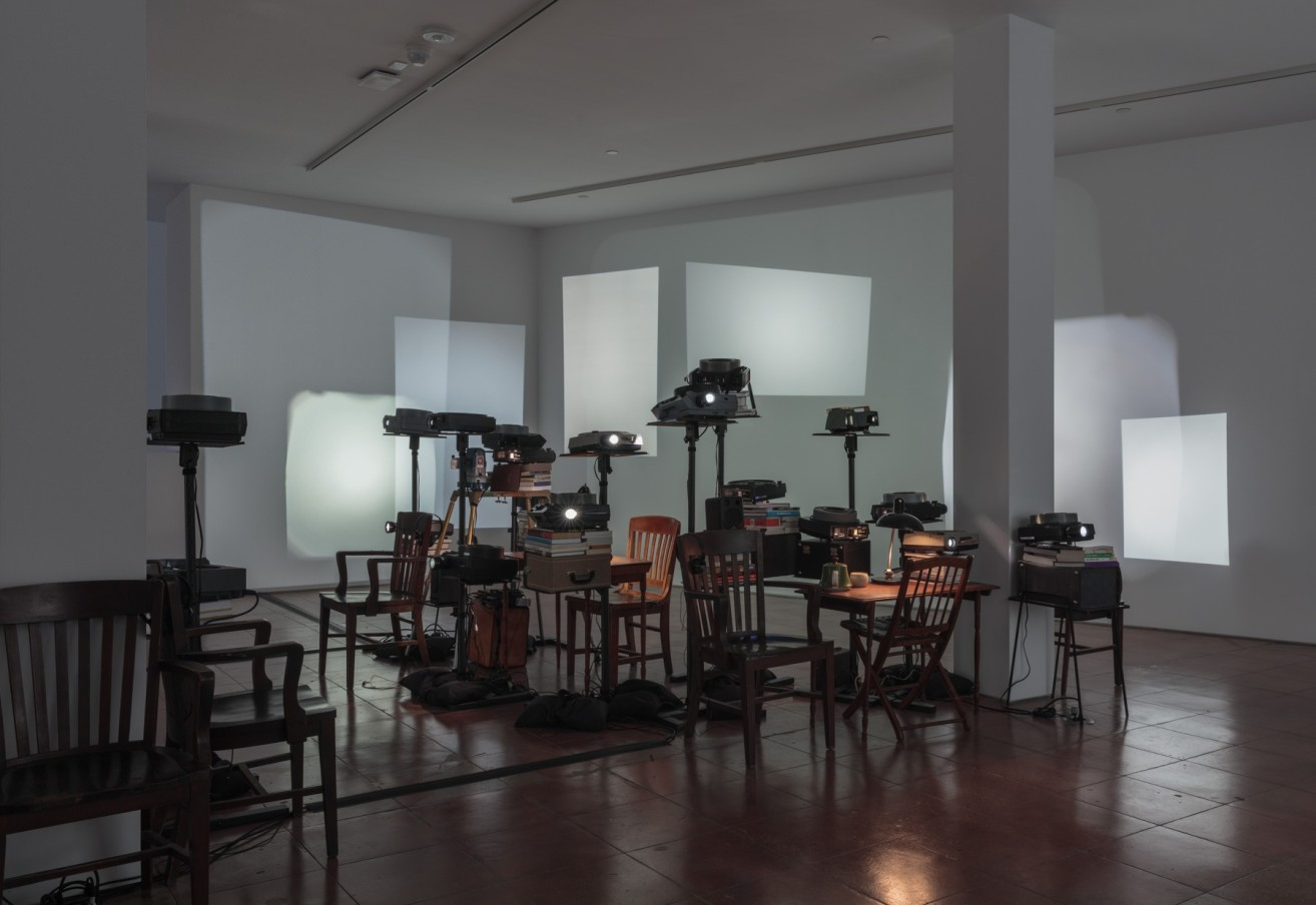 Andrea Geyer Feeding the Ghost, 2019 Slide projectors, projector stands, books, sandbags, furniture, lamps, 60 minute voice over Dimensions vary with installation Edition of 2 plus 1 exhibition copy