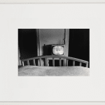 Framed black and white horizontal photograph of a small hotel bedroom with a television showing a baby's face