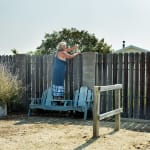 Horizontal color photograph of a woman holding her wine glass over a backyard fence