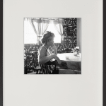 Framed black and white lateral portrait of a woman sitting in a dining room, with patterned wallpapered walls and a large window
