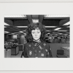 Framed back and white frontal photograph of a woman in a geometric patterned working on a desk, in a large office space
