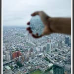 Framed vertical color photograph of an outstretched hand holding a mirror from the window of a high building with a sprawling city background