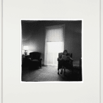 Framed black and white square photograph of a lady sitting in an armchair and reading a newspaper in a rooming house parlor, there is an open door in the background letting a lot of light in through the moving sheer blinds