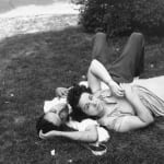 Black and white photograph of a couple laying on the grass of Central Park in New York