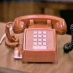 Still of a video piece, depicting a pink push button telephone on a table top