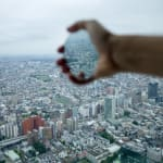 Vertical color photograph of an outstretched hand holding a mirror from the window of a high building with a sprawling city background