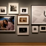 Installation view of a gallery wall with various black and white and color photographs arranges in an eclectic manner