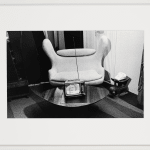 Framed black and white horizontal photograph of a small television with an antenna showing the face of a woman in distress, in a living room with an armchair in the background