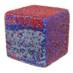 A foam cube densely covered in blue and silver sequins and blue beads.
