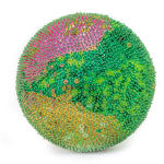 A foam sphere covered in green sequins and beads. There is a section of pink sequins across the top and a section of yellow across the bottom.
