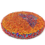 """A thick foam disc (called a """"pizza""""), the face of which is covered in gold sequins and red beads, except for a quarter that is blue. The rim of the disc is blue sequins with red beads."""