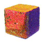 A foam cube densely covered sequins and beads. The front face has pink and gold sequins, some of which are shaped like stars, and yellow beads. The right face is entirely purple and the top is pink and yellow.