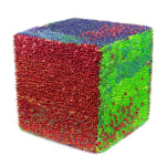 A foam cube densely covered in sequins and pins. The front face is completely red, while red shifts to green on the right side and to blue on the top.