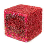 A foam cube densely covered in red and pink sequins and pins