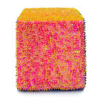 One face of a foam cube densely covered pink and yellow sequins and beads.