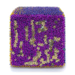 One face of a foam cube densely covered sequins and beads, most of which are purple but some sequins are gold and shaped like stars.
