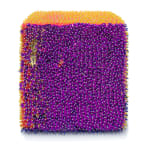 One face of a foam cube densely covered purple sequins and beads.