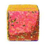 One face of a foam cube densely covered in pink and gold sequins, some of which are shaped like stars, and yellow beads.