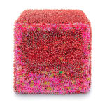 One face of a foam cube densely covered in red sequins and pins, the edges are covered in pink sequins.