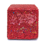 One face of a foam cube densely covered in red sequins and pins with a patch of pink across the top.