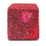 One face of a foam cube densely covered in red sequins and pins with a patch of pink towards the top.