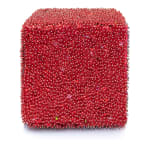 One face of a foam cube densely covered in red sequins and pins