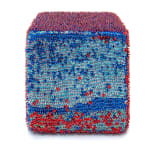 One face of a foam cube densely covered in blue sequins and red and blue beads across the top with a scattering of red sequins across the bottom.