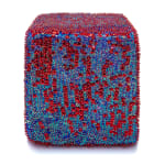 One face of a foam cube densely covered in red and blue sequins and beads.