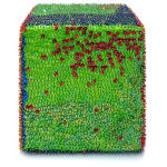 One face of a foam cube densely covered in red and green sequins.