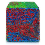One face of a foam cube densely covered in red and blue sequins.