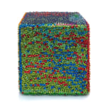 One face of a foam cube densely covered in blue, red, and green sequins.