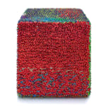 One face of a foam cube densely covered in red with a barely visible layer of green beneath.