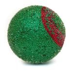 A foam sphere covered in green sequins and beads. A circle at the center, like the iris of an eye, is densely red and shifts to green at its core.