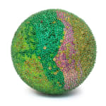 A foam sphere covered in green sequins and beads that shift in and out of pink and yellow bands.