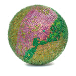 A foam sphere covered in green sequins and beads with a large section of pink sequins down the center.