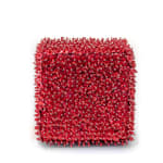A brick shape made of foam and densely covered in red sequins and beads.