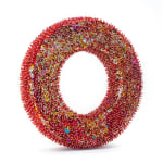 """A foam """"O"""" shape densely covered in gold sequins and red beads."""